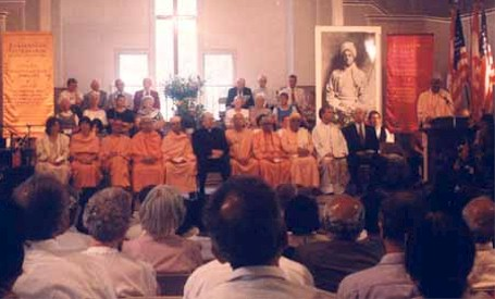 Visiting Swamis, religious leaders of different faiths, and musical artists seated in front of a crowd.